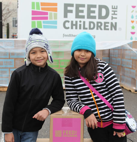 boy and girl with Feed the Children box