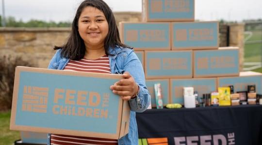 Girl holding Feed the Children Box