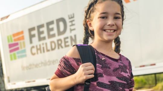 Girl carrying backpack in front of truck
