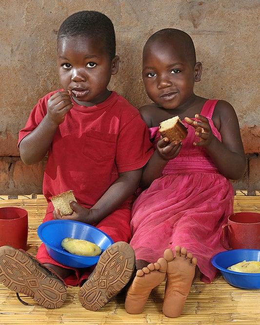 Two children eating bread