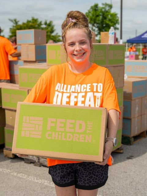 Feed the Children volunteer with box
